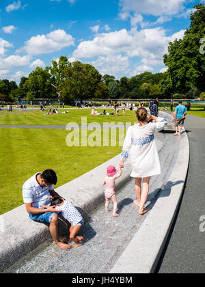 People Enjoying Sunshine, Princess Diana Memorial Fountain, Hyde Park, London, England - Stock Photo