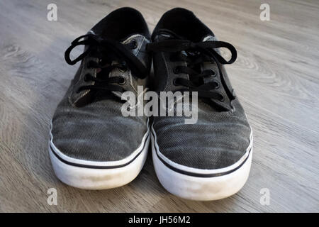 A pair of gray sneakers sitting on a vinyl plank floor. - Stock Photo