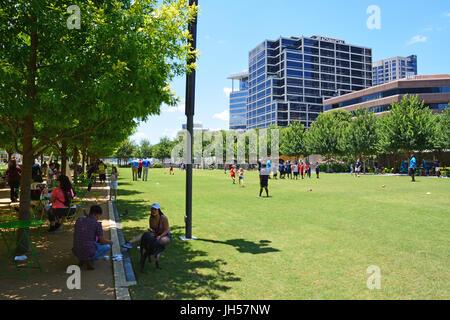 Residents escape the mid day heat under the shade of oak trees at Klyde Warren Deck Park in downtown Dallas Texas - Stock Photo