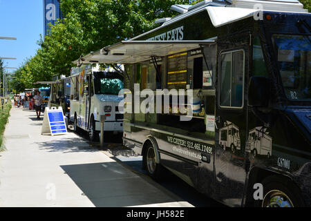 Food trucks line up during the day next to Klyde Warren Park in downtown Dallas - Stock Photo