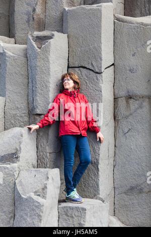 Tourist posing on the large basalt columns at Reynisfjara beach in Iceland - Stock Photo