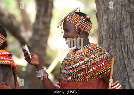 LOIYANGELENI, KENYA - May 18. A Samburu woman uses her mobile phone during the rehearsals of the Lake Turkana Festival - Stock Photo