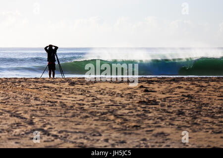 A photographer watches from the beach as a surfer gets barrelled on a perfect wave a surf break in Australia. - Stock Photo