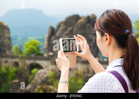 Young asian female tourist take photographs with mobile phone of famous Bastei rock formation and bridge in Saxon - Stock Photo