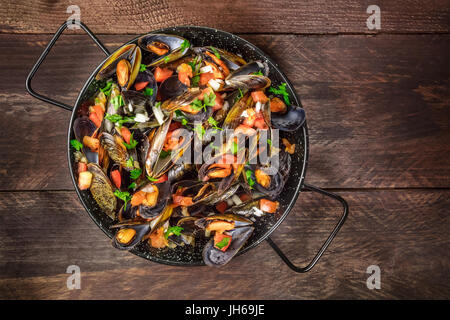 Skillet of marinara mussels on rustic background with copyspace - Stock Photo