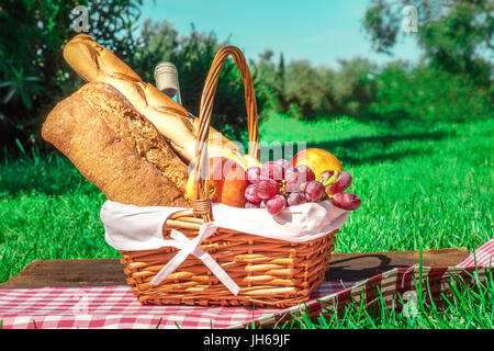 Picnic hamper with bread, fruit, and wine on green lawn - Stock Photo