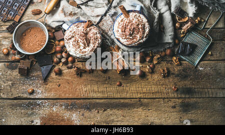 Hot chocolate with whipped cream and cinnamon sticks served with anise stars, different nuts and cocoa powder on - Stock Photo