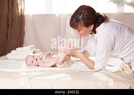 the little boy baby doctor doing massage - Stock Photo