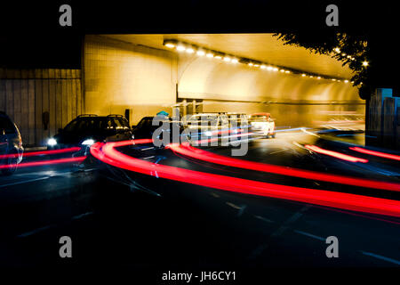 Night traffic on city streets. Cars queued at tunnel exit waiting at intersection while driving vehicles moving - Stock Photo