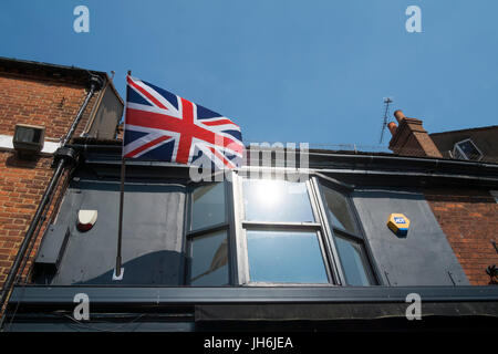 The Union flag (aka Union Jack) flying from a building in Eton, U.K. - Stock Photo