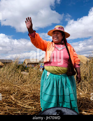 UROS ISLANDS, PERU - CIRCA October 2015: Woman from the Uros waving hands and welcoming people in the floating Islands - Stock Photo