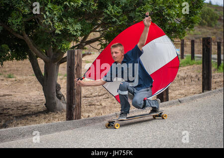 Parachute downhill skateboarder has sail full of wind as he crouches in goofy foot stance. - Stock Photo
