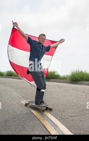 Parachute downhill skateboarder has sail full of wind as he rides the nose of board. - Stock Photo