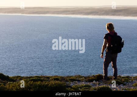 A hiker stops to look at a distant view of a beautiful coastline from a high view point above the sea in southern Australia.