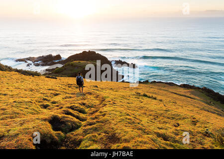 A person on a grassy headland watches the sunrise over the sea and a beautiful coastline in Australia. - Stock Photo