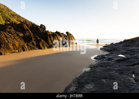 A person stands alone on a remote beach in Australia and watches the bright morning sun light the coastline and - Stock Photo