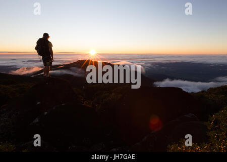 A hiker watches a beautiful sunrise on from the summit of a mountain above the clouds in Australia. - Stock Photo