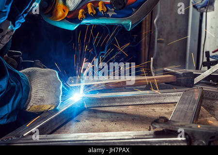 A young man welder in a blue construction overall, in a welding mask and construction gloves, weld a metal product - Stock Photo