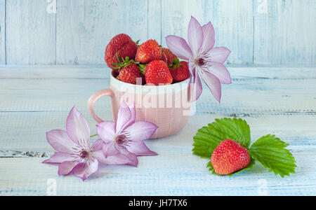 Ripe strawberry in a Cup pink ceramic . Pink flowers of clematis. A light blue background. The horizontal frame. - Stock Photo