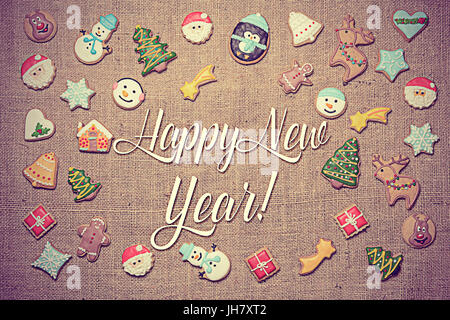 Happy New Year! Holiday greeting written among decorative gingerbread cookies. Vintage look added in post-processing. - Stock Photo