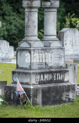 Tattered Confederate flag and Confederate Veteran maker next to gravestone memorial at Lawrenceville Historic Cemetery - Stock Photo