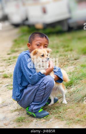 Lobesa Village, Punakha, Bhutan - September 11, 2016: Little Bhutanese boy hugging a German Spitz puppy in the street. - Stock Photo