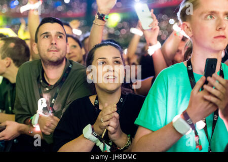 Fans in the crowd watch Coldplay perform at the Principality Stadium, Cardiff, on 11th July 2017. - Stock Photo