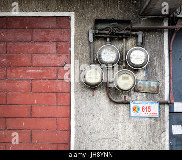 Manila, Philippines - Dec 20, 2015. Old electric meters on the wall at house in Manila, Philippines. Manila is a - Stock Photo