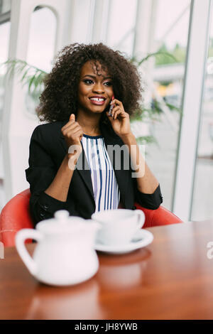 Stylishly dressed afro-american girl is talking via the cellphone in the cafe. - Stock Photo