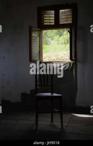 Chair in front of an open window with a mosquito netting. A dark indoor setting: shabby wall, rustic wood plank - Stock Photo