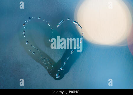 The inscription of the heart on the sweaty glass at night. - Stock Photo