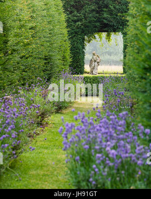 Sculpture of woman in garden with lavender - Stock Photo