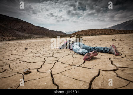 Traveller lays on the dried ground - Stock Photo