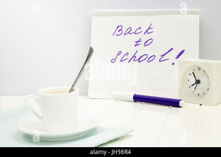 Concept back to school message written on notebook. Morning set with alarm clock and cup of coffee. Copy space. - Stock Photo
