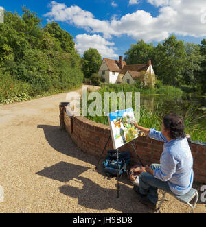 Artist painting Willy Lott's Cottage by flatford mill where John Constable painted the Haywain. - Stock Photo