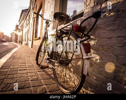 Bruges, Belgium. 5th June, 2015. A bile at sunset on a side street in Bruges, Belgium. Credit: Alex Edelman/ZUMA - Stock Photo