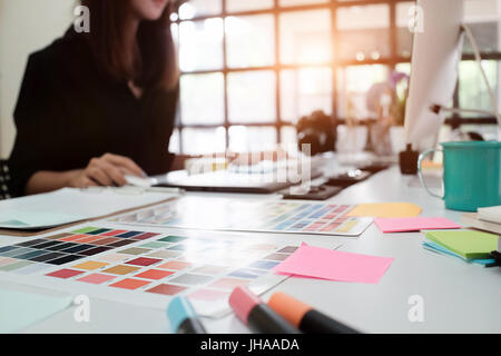 Selective focus on creative table and woman graphic design blur in background with vintage tone. - Stock Photo