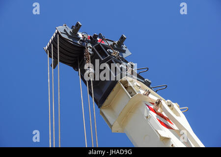 truck crane detail boom with hooks and scale weight above blue sky - Stock Photo