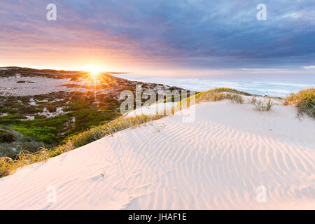 The sun bursts above the horizon, illuminated the sand dunes and surrounding coastline in this beautiful seascape. - Stock Photo