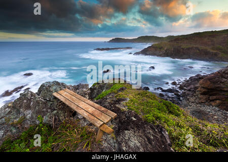 An empty wooden bench with a view over a beautiful rocky coastline at sunset in Australia. - Stock Photo