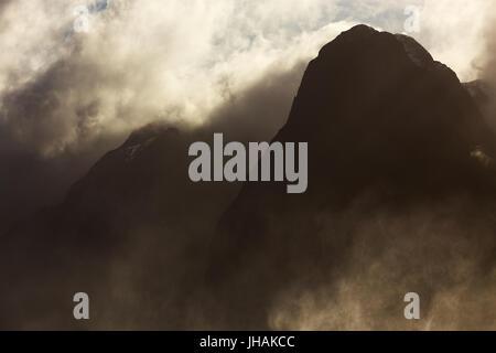 Ominous mountain peaks shrouded in illuminated cloud and mist. - Stock Photo