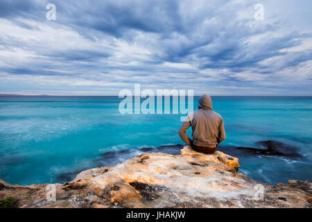 A man sits on the edge of a rugged limestone cliff and looks over a stormy ocean view in South Australia. - Stock Photo