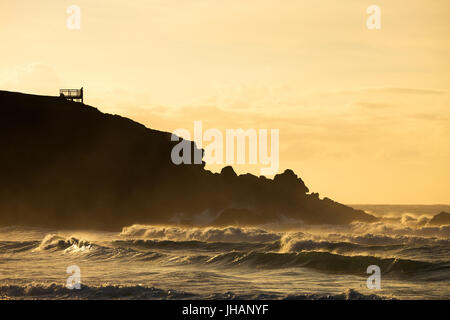 A silhouetted person watches the waves breaking on the beach in golden morning light from a viewing platform. - Stock Photo