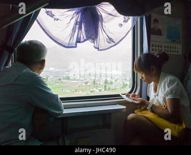 Young Chinese girl sitting on train eating, while older man looks out of carriage window at scenery. Yunnan, China - Stock Photo