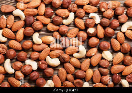 Different nuts on a wooden table. Almond, hazelnut and cashew. Background with nuts. - Stock Photo
