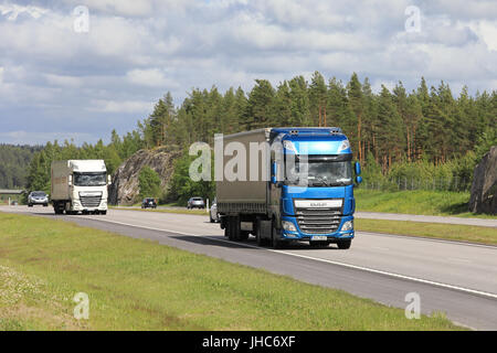 Blue and white DAF XF semi trailer trucks transport goods along motorway among traffic on a beautiful day of summer. - Stock Photo
