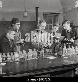 1950s, historical, post-war England, UK, science laboratory at Mill Hill School, North London, England, UK, a traditional British fee-paying boys only boarding school. Picture shows boys taking down notes as the male teacher demonstrates to them how different chemicals react when mixed together.
