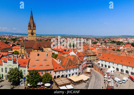 Sibiu,Romania.Old roofs of Lutheran cathedral tower and Small Square (Piata Mica). - Stock Photo