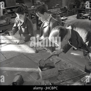 1950s, historical, England, UK, two male students wearing army uniform and teacher doing metal work in a tool shop - Stock Photo