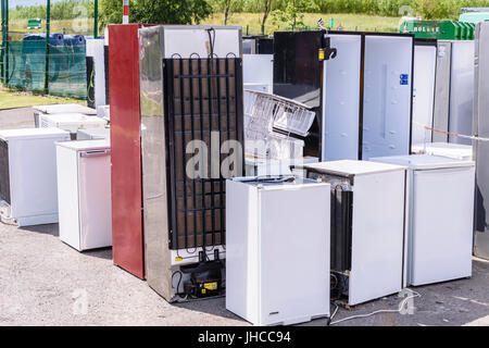 Broken refrigerators at a recycling centre, waiting to be disposed of and recycled in an environmentally friendly - Stock Photo